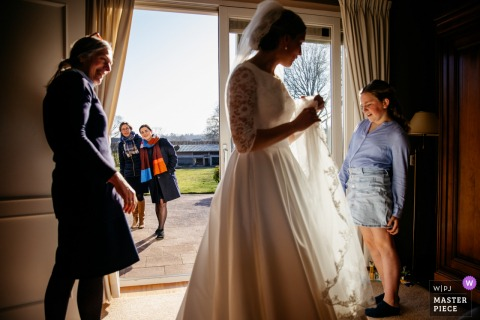A top wedding photographer in Netherlands captured this picture of the bride showing her dress to guests while waiting for the groom to arrive