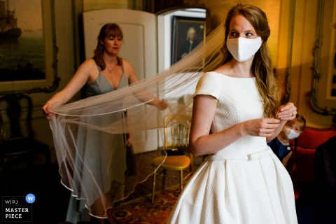 A top wedding photographer in Utrecht captured this picture of the bride getting ready wearing a mask
