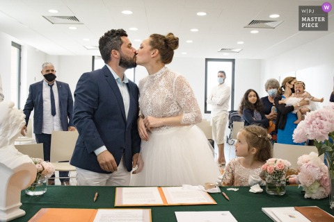Best wedding photography from Puyjaudran Town Hall showing a pic showing the bride and groom kiss under the watchful eye of their daughter