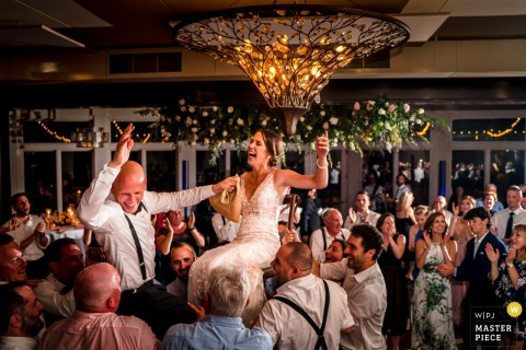 Best wedding photography from Virginia at the Stone Tower Winery showing A couple is lifted in the air during the Hora dance