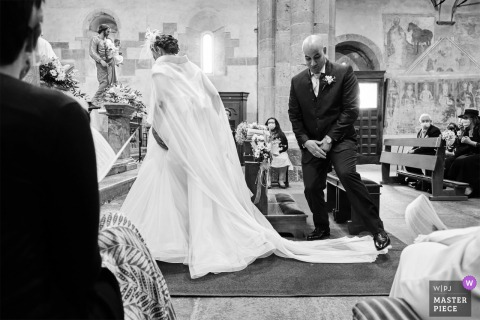 Best Italy wedding photography from Brebbia showing a pic of the Groom making a small leap to avoid the Brides dress