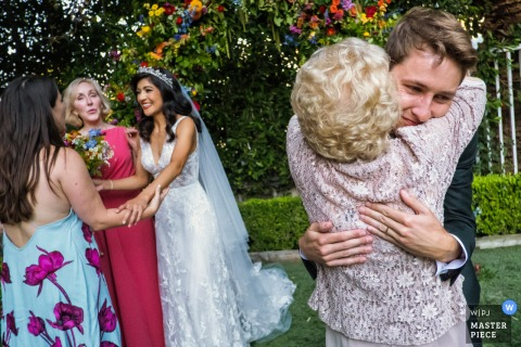 The Lombardi House, Los Angeles, California wedding photo showing Tears run down on the grooms face as he hugs his grandmother