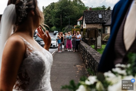 A church in East Yorkshire, UK wedding reportage photography showing  The bride waves to a waiting crowd as she arrives at the ceremony