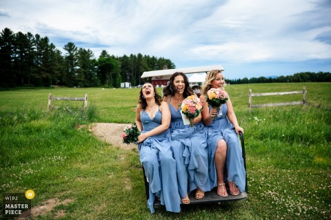 Wedding photography from Morrisville, Vermont showing The bridesmaids catch a bumpy ride on a golf cart