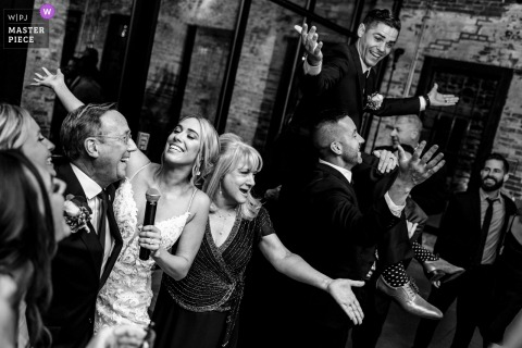 Mt. Washington Mill Dye House, Baltimore indoor wedding reception party award-winning picture showing Bride and parents singing at the venue while groom is lifted up in the air. The world's most skilled wedding photographers are members of the WPJA