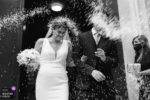 Church Genoa, Italy nuptial day award-winning image of the bride and groom getting rice thrown at them after the ceremony. The world's best wedding photography competitions are hosted by the WPJA