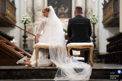Siracusa indoor marriage ceremony award-winning image showing a real funny moment at the church altar. The world's best wedding picture competitions are featured via theWPJA