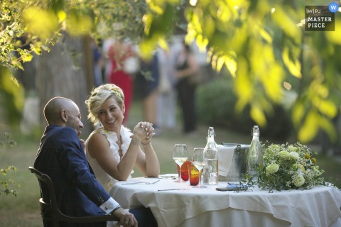 Ravenna outdoor marriage reception party award-winning photo that has recorded the bride and groom at the table during the reception. The world's top wedding photographers compete at the WPJA
