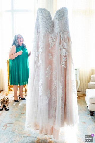 Rhodes Hall, Atlanta nuptial day award-winning image of the mother of the bride laughing as the bride's dress is hanging from the chandelier. The world's best wedding photography competitions are hosted by the WPJA