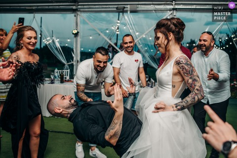 Sofia, Bulgaria outdoor marriage reception party award-winning photo that has recorded the groom gesturing - Come on, baby. The world's top wedding photographers compete at the WPJA