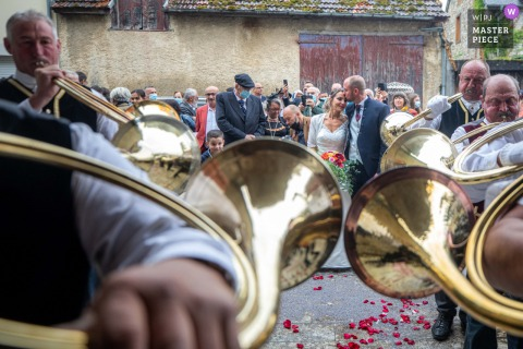 Occitanie outdoor marriage ceremony award-winning image showing Traditional musicians are playing music for bride and groom with emotions. The world's best wedding photo contests presented by the WPJA