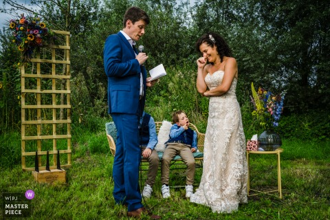 Limburg outdoor marriage ceremony award-winning image showing the bored kids during the vows. The world's best wedding photo contests presented by the WPJA