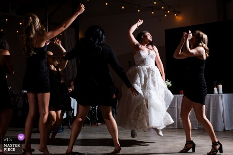 Clay Venues, Colorado Springs indoor wedding reception party award-winning picture showing the bride and her besties jump for joy while celebrating at the reception. The world's most skilled wedding photographers are members of the WPJA