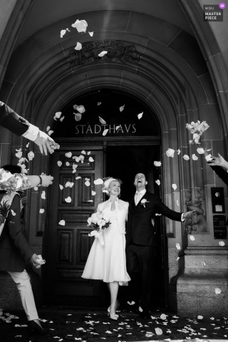 Switzerland nuptial day award-winning image of bride and groom celebrating under flower petal showers