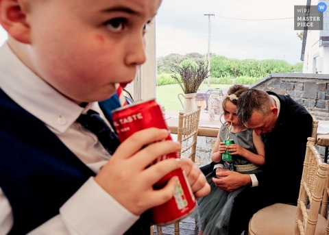 Kilrush, Ireland nuptial day award-winning image of a father bowing his head in despair of moody child whilst the sibling happily drinks his coke.The world's best wedding photography competitions are hosted by the WPJA