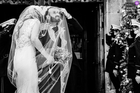 Iglesia de San Ildefonso, Jaén nuptial day award-winning image of groom taking cover under the brides veil with military honors behind