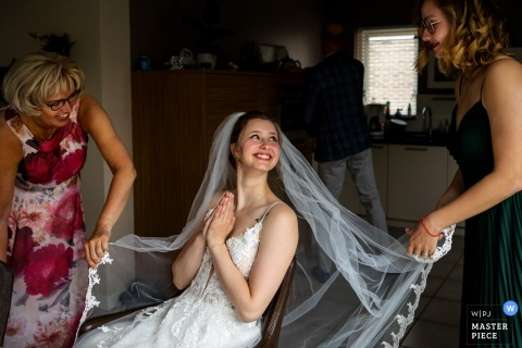 Amsterdam marriage preparation time award-winning picture capturing an excited bride waiting for the arrival of the groom with sister & mother. The world's best wedding image competitions are held by the WPJA