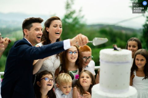 Tenuta Colle Paradiso, Erbusco outdoor marriage reception party award-winning photo that has recorded the cutting of the wedding cake surrounded by the little guests. The world's top wedding photographers compete at the WPJA