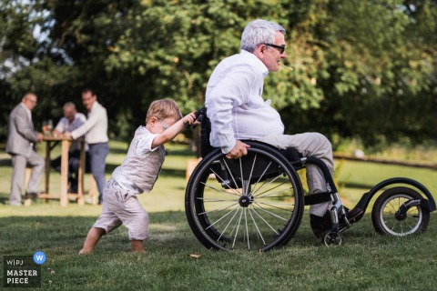 Château Saint Loup en Albret, France outdoor marriage reception party award-winning photo that has recorded a small boy pushing man in wheelchair on the grass