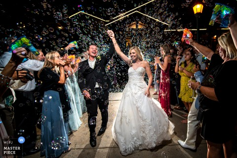 The Estes Park Resort, Colorado outdoor marriage reception party award-winning photo that has recorded a bride and groom bubble send off