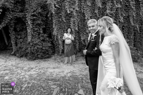 Riserva Naturale Orientata La Timpa outdoor marriage ceremony award-winning image showing These spouses are walking along a nature path and a woman waiting to become a mother looks at them with a satisfied air as they pass in front of them.