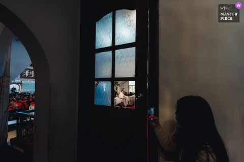 Fujian indoor marriage ceremony award-winning image showing The bridesmaid used her mobile phone to record the newcomer at the ceremony from the corner