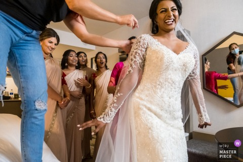 Novi Sheraton Hotel, Michigan marriage preparation time award-winning picture capturing the Bride getting zipped into her dress and everyone is thrilled for her.