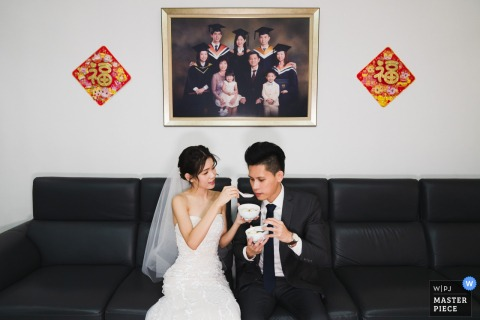 Singapore nuptial day award-winning image of the Bride feeding rice ball to her groom during a Chinese ceremony