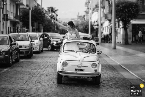 Lazio nuptial day award-winning image of The bride greeting people from a small car on the way to the restaurant