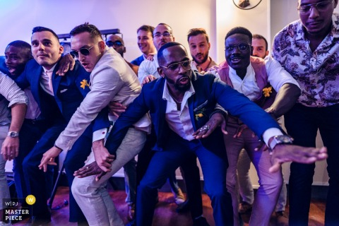 Domaine de l'Orangerie, France indoor wedding reception party award-winning picture showing Grooms friends during a dance battle