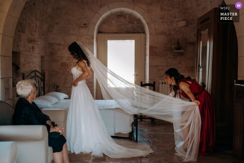 Puglia marriage preparation time award-winning picture capturing the bride getting veil fixed