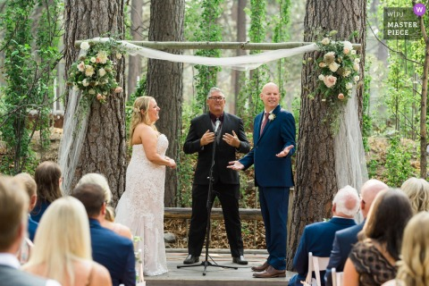Revive Coffee and Wine - South Lake Tahoe outdoor marriage ceremony award-winning image showing A groom makes a comment to the crowd of guests watching their ceremony while the bride laughs.