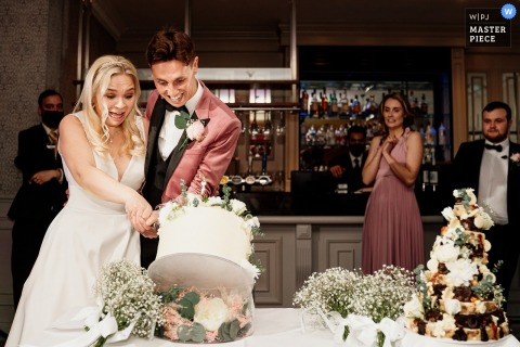 Mottram Hall indoor wedding reception party award-winning picture showing Bride and groom cutting the cake and the cake falls
