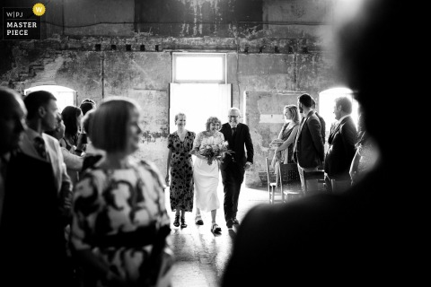 Asylum Chapel, London indoor marriage ceremony award-winning image showing Bride walking up the aisle with her parents and gets the giggles