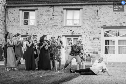 Nomades Lodge, France outdoor marriage reception party award-winning photo that shows Grandma tried to get the bouquet. The world's top wedding photographers compete at the WPJA