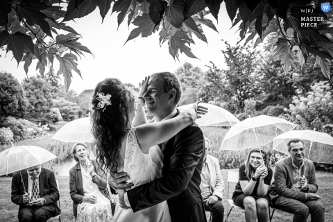Landgoed Tielen, Hoeven outdoor marriage award-winning image showing that During the ceremony in the rain, the bride wipes the rain from the groom
