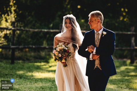 Tenuta Pantano Borghese- Rome outdoor marriage ceremony award-winning image showing the bride is entering at the ceremony with her father. The world's best wedding photo contests presented by the WPJA