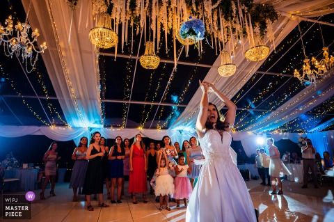 Marina Cape, Aheloy, Bulgaria indoor wedding reception party award-winning picture showing the Bouquet tossing. The world's most skilled wedding photographers are members of the WPJA