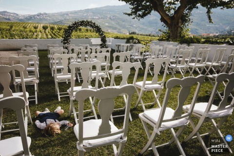 Peso da Régua - Quinta da Pacheca - Portugal outdoor marriage ceremony award-winning image showing a small boy sleeping by the outdoor chairs. The world's best wedding photo contests presented by the WPJA