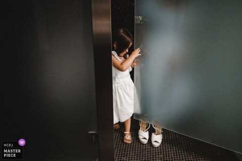 Viana do Castelo - Portugal marriage preparation time award-winning picture capturing a little flower girl with a glass door. The world's best wedding image competitions are held by the WPJA