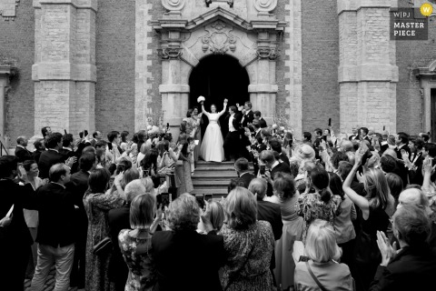 Begijnhof Lier nuptial day award-winning image of the couple exiting church surrounded by celebrating guests. The world's best wedding photography competitions are hosted by the WPJA
