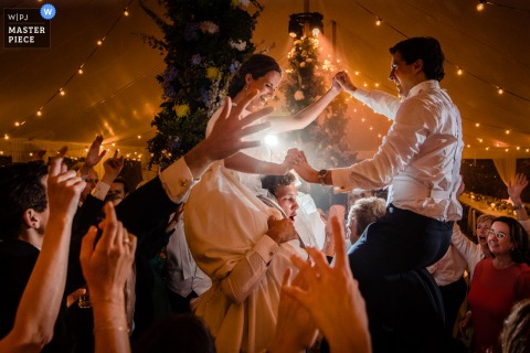 Lier indoor wedding reception party award-winning picture showing bride and groom dancing on guests shoulders. The world's most skilled wedding photographers are members of the WPJA