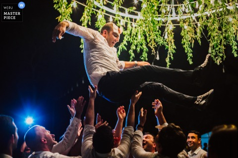 Bodrum, Turkey outdoor marriage reception party award-winning photo that has recorded a Groom in air under trees and lights. The world's top wedding photographers compete at the WPJA