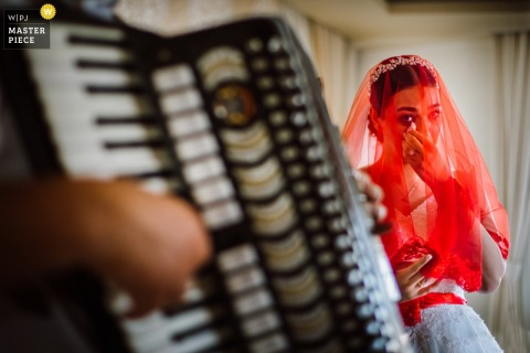 Bodrum, Turkey nuptial day award-winning image of Bride saying goodbye to her family with traditional accordion goodbye song. The world's best wedding photography competitions are hosted by the WPJA