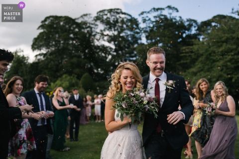 Eggington House, UK outdoor marriage ceremony award-winning image showing A confetti moment outdoors. The world's best wedding photo contests presented by the WPJA