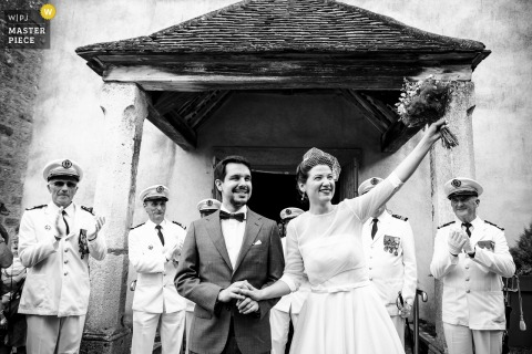Image primée de la cérémonie de mariage à Lyon montrant la sortie de l'église des mariés avec une garde d'honneur militaire. Les meilleurs concours de photos de mariage au monde sont présentés via le WPJA