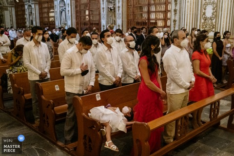 Santo Domingo Church, Oaxaca City indoor marriage ceremony award-winning image showing a Sleeping flowergirl during the ceremony. The world's best wedding picture competitions are featured via theWPJA