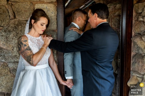Mt. Woodson Castle indoor marriage ceremony award-winning image showing The minister says a prayer with the bride and groom just prior to their wedding ceremony.