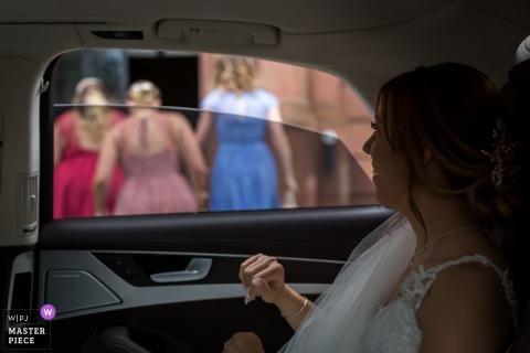 Image primée du jour des noces de Strasbourg de la mariée dans une voiture devant la mairie. Les meilleurs concours de photographie de mariage au monde sont organisés par la WPJA