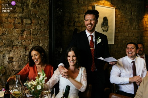 The Elgin, London indoor wedding reception party award-winning picture showing the Groom giving his speech whilst holding his smiling wifes hand. The world's most skilled wedding photographers are members of the WPJA